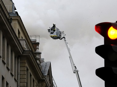 A firefighter stands atop a fire ladder as a fire engulfed the top floor of Paris' Ritz Carlton hotel. AP