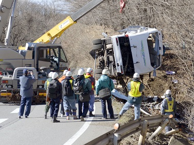 A damaged bus is lifted by crane on a mountain road in Karuizawa, Nagano prefecture on Friday. AP