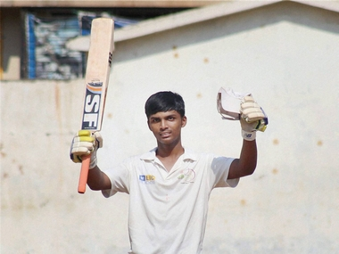 Pranav Dhanawade raises his bat, after a reaching a 1000 runs. PTI