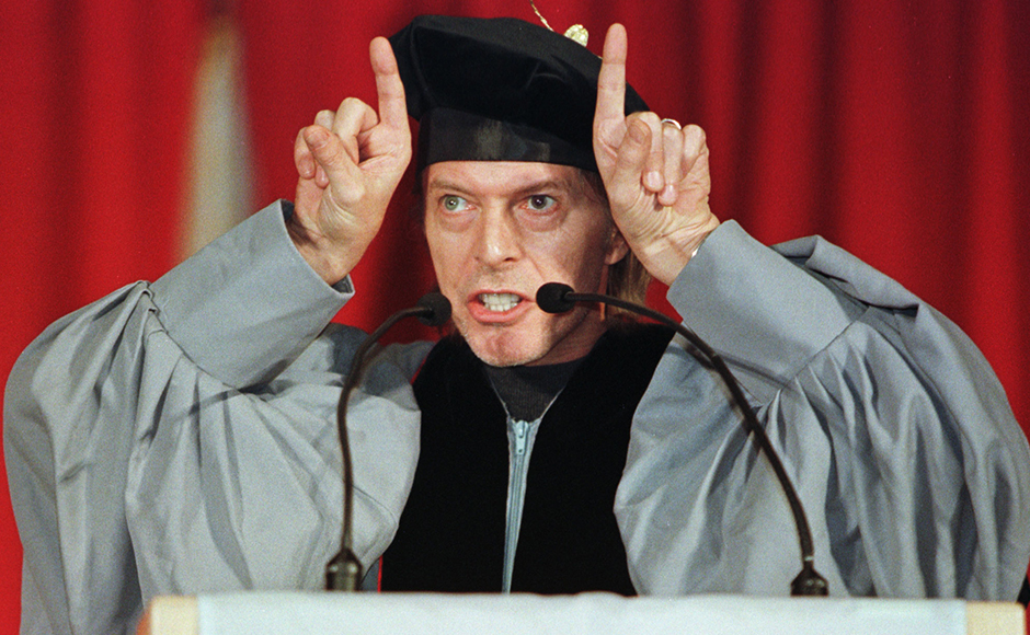 Rock musician David Bowie jokingly makes devils horns in front of his head as he delivers the commencement address May 8 at the 1999 graduation ceremonies of the Berklee College of Music in Boston. Bowie, who joked about the various roles of musicians, spoke to more than 600 graduates about his long friendship with the late British rock star [John Lennon.] Reuters