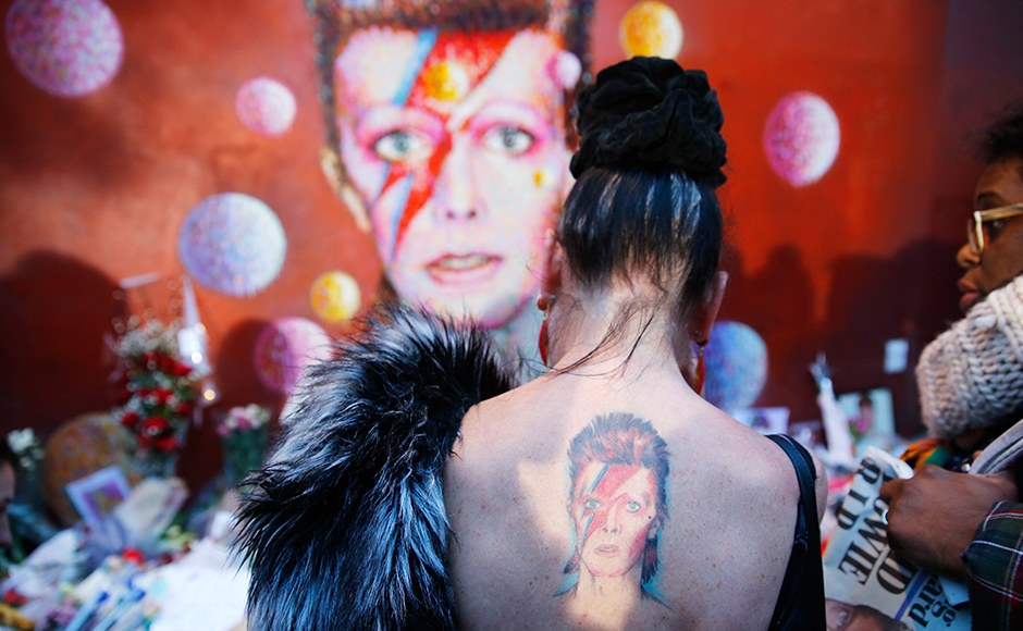 """A woman with a Ziggy Stardust tattoo visits a mural of David Bowie in Brixton, south London, January 11, 2016. David Bowie, a music legend who used daringly androgynous displays of sexuality and glittering costumes to frame legendary rock hits """"Ziggy Stardust"""" and """"Space Oddity"""", has died of cancer. REUTERS/Stefan Wermuth"""