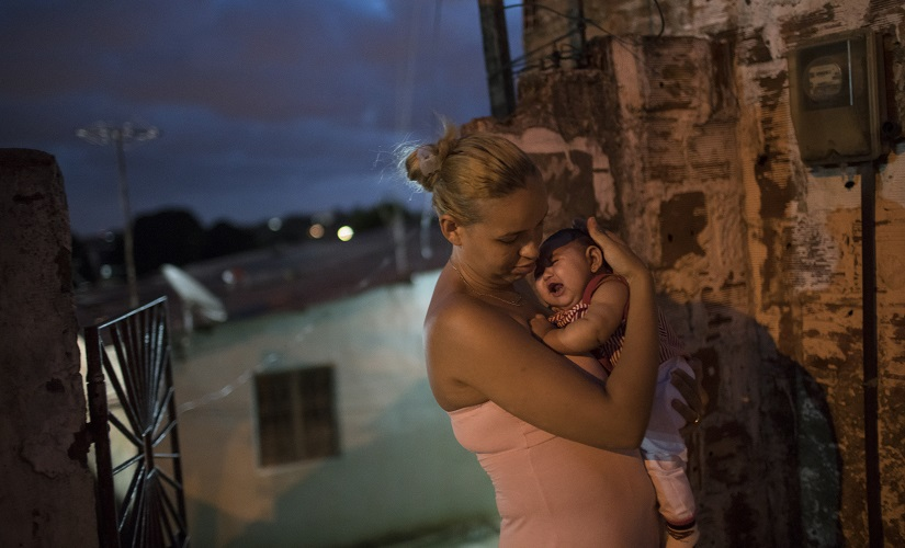 Gleyse Kelly da Silva, 27, holds her daughter Maria Giovanna, who was born with microcephaly, outside their house in Recife, Brazil. AP