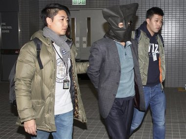 Deyun Shi, 44, center, is escorted by police officers, was taken into custody in Hong Kong on Sunday, AP