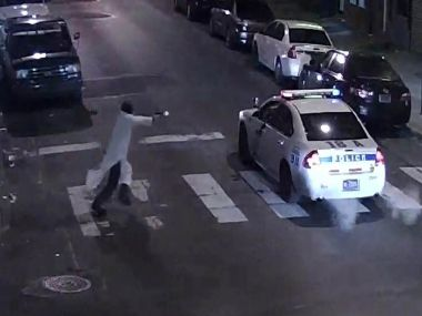 This video still image from the Philadelphia Police Department shows the shooting suspect and police car. AFP/ Philadelphia Police Department