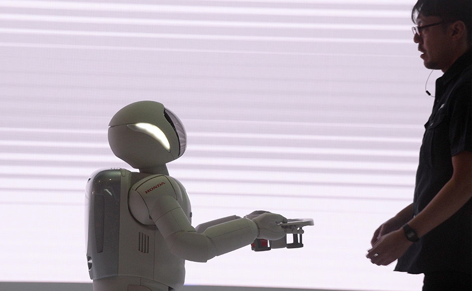 Honda's robot 'Ashimo' shows its skills by carrying a glass of water at Auto Expo 2016, in Greater Noida some 45kms east of New Delhi on February 4, 2016. India's flagship auto show opened its doors in New Delhi with a new batch of diesel-guzzling SUVs on proud display, despite industry uncertainty about a pollution crackdown targeting motorists in the capital. More than 80 vehicle launches were expected at the Auto Expo 2016, the biggest edition in the show's 30-year history, with the Fiat Chrysler-owned Jeep making its India debut and hoping to capitalise on the popularity of sports utility vehicles. . AFP PHOTO / Prakash SINGH