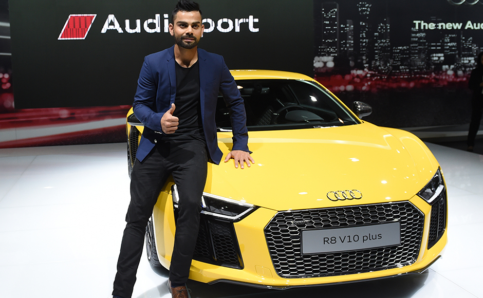 Indian cricketer Virat Kohli poses with the newly launched Audi R8 V10 plus at the Indian Auto Expo 2016 in Greater Noida on the outskirts of New Delhi on February 3, 2016. India's flagship auto show opened its doors in New Delhi February 3, with a new batch of diesel-guzzling SUVs on proud display despite industry uncertainty over a pollution crackdown targetting motorists in the capital. AFP PHOTO / SAJJAD HUSSAIN