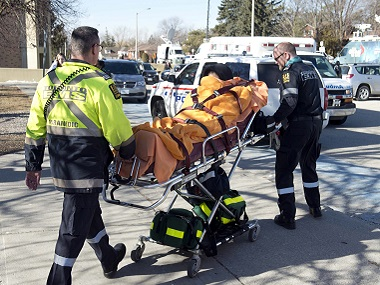 An unidentified victim is taken away on a stretcher by emergency personnel remove following a stabbing incident at Dunbarton High School in Pickering, Ontario on Tuesday. AP