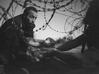 "This picture released by the World Press Photo was taken by Australian freelance photographer Warren Richardson on 28 August, 2015 in Roszke, Hungary. It shows a refugee passing a baby under a barbed wire fence at the Hungarian-Serbian border. It is titled ""Hope for a New Life"". Warren Richardson / World Press Photo / AFP"