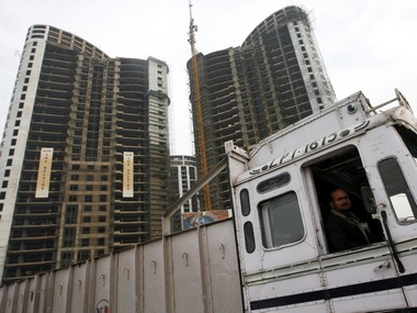 A truck driver looks out at the construction site of a residential apartment building by Indian property developer DLF Ltd. in Gurgaon January 27, 2010. Shares in DLF Ltd, India's top listed real estate firm, rose more than 3 percent on Thursday after it reported a sequential rise in quarterly profit, signalling a recovery in the realty market was gaining momentum. Picture taken January 27, 2010. REUTERS/Adnan Abidi (INDIA - Tags: BUSINESS)