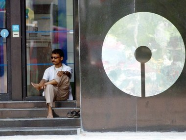 An Indian man sits beside an ATM counter of the State Bank of India, (SBI) in Kolkata, 05 April 2006, as thousands of employees of the bank continued on the fourth day of their nationwide strike.   The Indian Government refused to accept the demand of striking SBI employees for an enhanced pension package.  SBI is India's largest commercial bank, which handles 19 per cent of total deposits and 30 per cent of customers in the banking industry through its some 9,000 branches.   AFP PHOTO/Deshakalyan CHOWDHURY