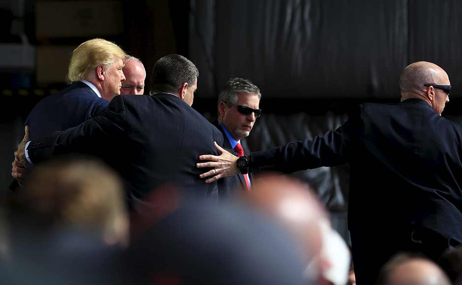 Secret Service agents surround U.S. Republican presidential candidate Donald Trump during a disturbance as he speaks at Dayton International Airport in Dayton, Ohio, March 12, 2016. REUTERS
