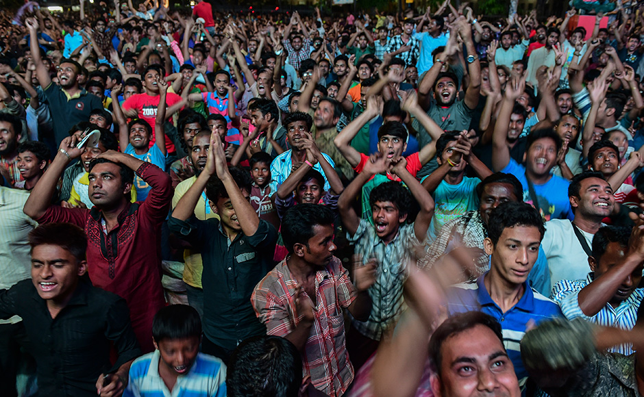 Bangladeshi cricket fans cheers as they watch the World T20 cricket tournament match between Bangladesh and India broadcast on a screen in a street in Dhaka on March 23, 2016, as the match takes place in the Indian city of Bangalore. / AFP / Munir UZ ZAMAN