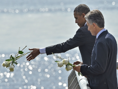 US President Barack Obama (L) and Argentinian President Mauricio Macri throw a bouquet of white flowers into the River Plate as they pay homage to Dirty War's victims. Getty Images