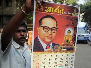 A man holding up an Ambedkar calendar. AFP