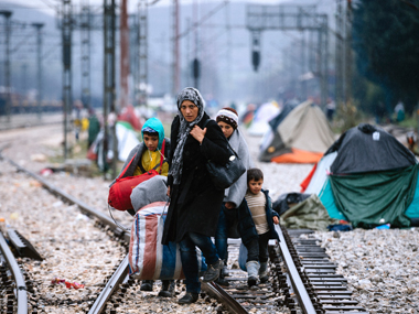 A woman and three children walk on railway tracks connecting Greece with western Europe at the Greek-Macedonian border near the Greek village of Idomeni on March 9, 2016, where thousands of refugees and migrants are trapped by the Balkan border blockade. AFP
