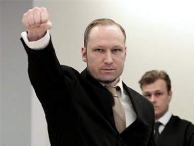 Anders Behring Breivik gestures as he arrives at the courtroom. AP