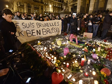 """People holding a banner reading """"I am Brussels"""" behind flowers and candles to mourn for the victims. AP"""