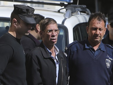 EgyptAir plane hijacking suspect Seif Eddin Mustafa, second left, is escorted by Cyprus police officers. AP
