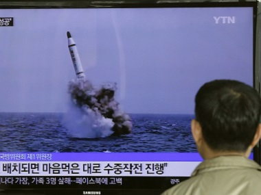 A South Korean man watches a TV news program showing an image published in North Korea's Rodong Sinmun newspaper of North Korea's ballistic missile believed to have been launched from underwater. AP