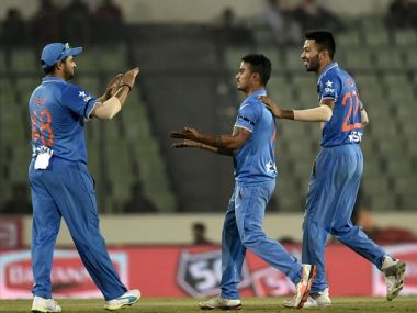 Suresh Raina and Hardik Pandya congratulate Pawan Negi on his first wicket. Getty Images