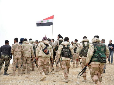 Syrian soldiers gather around a Syrian national flag in Palmyra. AP