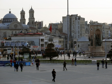 People walk in Taksim Square near the Saturday explosion site in Istanbul. AP