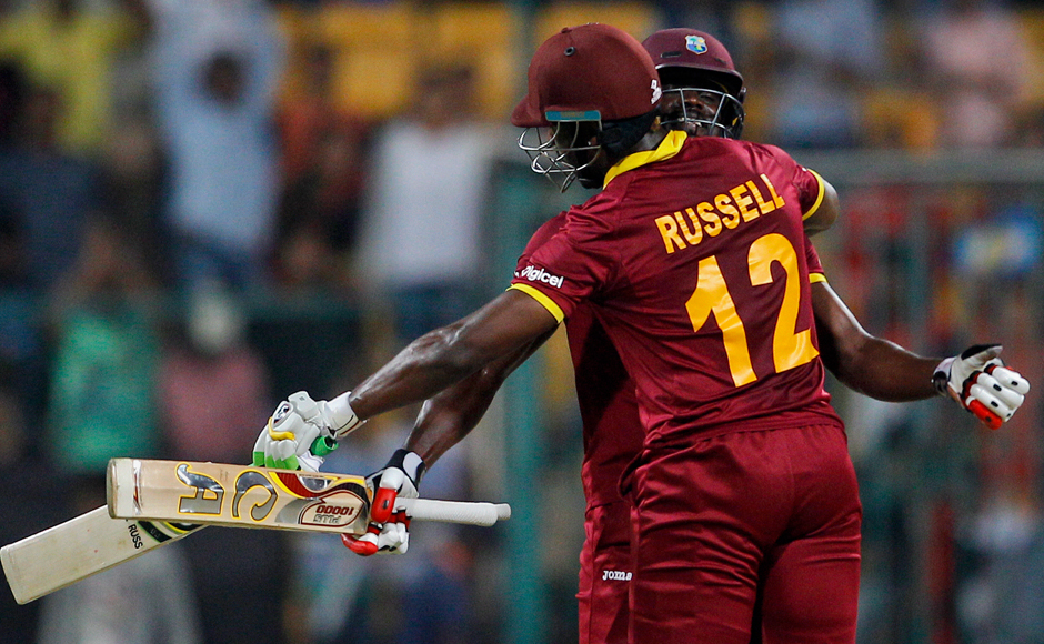 West Indies' Andre Fletcher, facing camera, hugs teammate Andre Russell to celebrate their team's win over Sri Lanka in the ICC World Twenty20 2016 cricket match in Bangalore, India, Sunday, March 20, 2016. West Indies won by 7 wickets. (AP Photo/Aijaz Rahi)