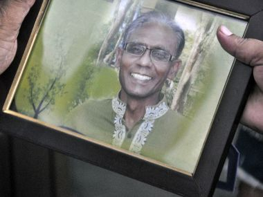 A man holds a portrait of Bangladeshi professor Rezaul Karim Siddique, who was hacked to death by unidentified attackers, in Rajshahi. AFP