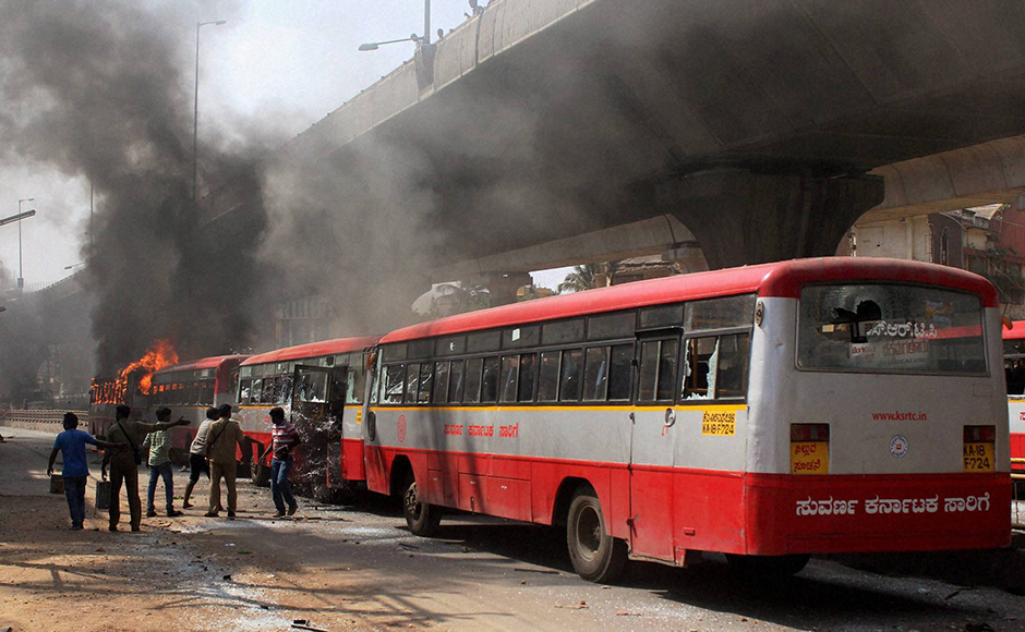 Charred buses which were torched by garment workers during a protest rally over EPF withdrawal norm, in Bengaluru on Tuesday. PTI Photo