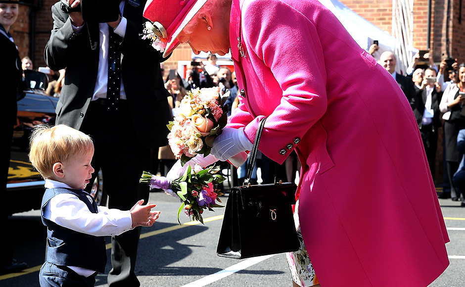 Queen Elizabeth II is presented with flowers as she leaves the Queen Elizabeth II delivery office in Windsor with Prince Philip, Duke of Edinburgh on April 20, 2016 in Windsor, Britain. The visit marks the 500th Anniversary of the Royal Mail delivery service. The Queen and Duke of Edinburgh are carrying out engagements in Windsor ahead of the Queen's 90th Birthday tommorow. REUTERS/Chris Jackson/Pool
