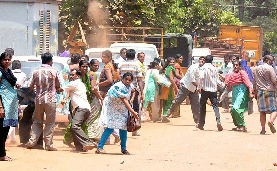 Agitated garment workers pelting stones during the protest rally over EPF withdrawal norm, in Bengaluru on Tuesday. PTI Photo