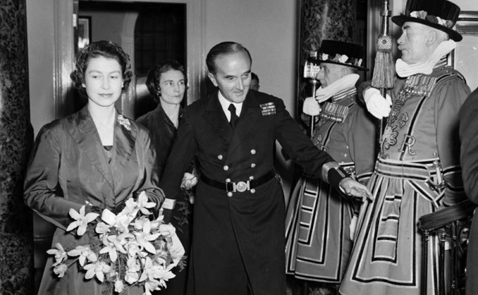 Queen Elizabeth II holding a bouquet of flowers as Captain G Curteis, Deputy Master of Trinity House, introduces her to the Yeoman of the Guard as they tour the rebuilt Trinity House on Tower Hill, October 21st 1953. (Photo by Reg Speller/Fox Photos/Getty Images)