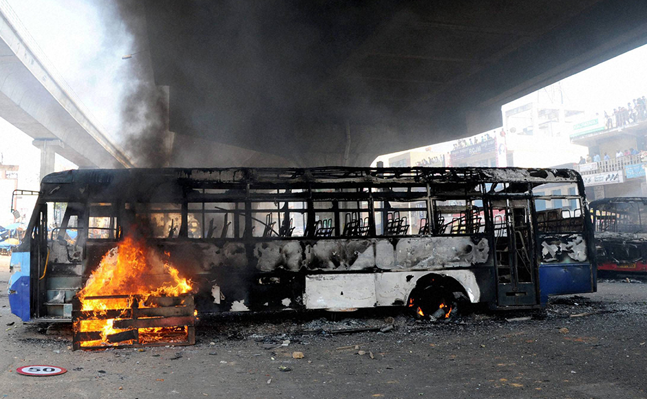 Charred buses which were torched by garment workers during a protest rally over EPF withdrawal norm, in Bengaluru on Tuesday. PTI Photo by Shailendra Bhojak