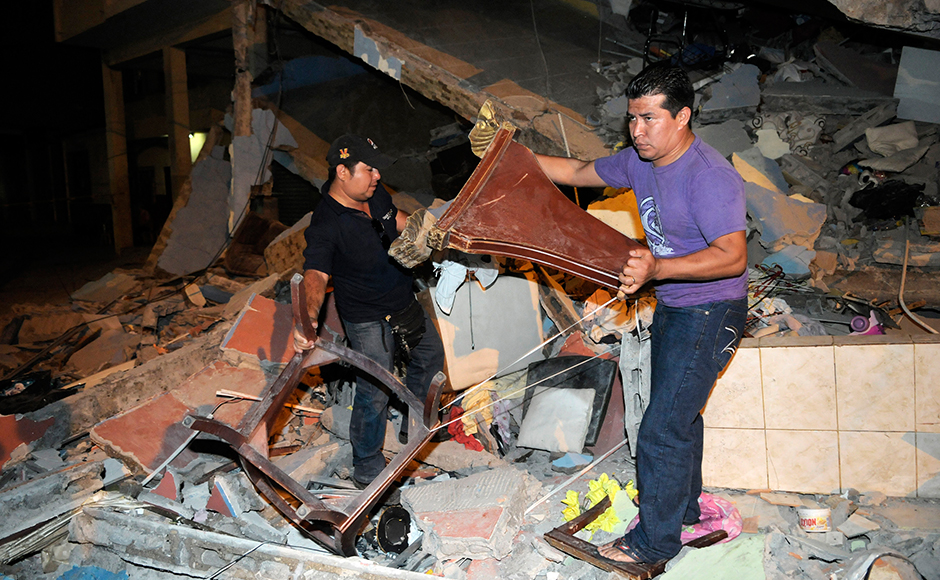 This picture shows two men removing debris from a fallen building after an earthquake in the city of Guayaquil on April 17, 2016. At least 77 people were killed when a powerful 7.8-magnitude earthquake struck Ecuador, destroying buildings and a bridge and sending terrified residents dashing from their homes, authorities in the Latin American country said on April 17. MARCOS PIN MENDEZ / AFP