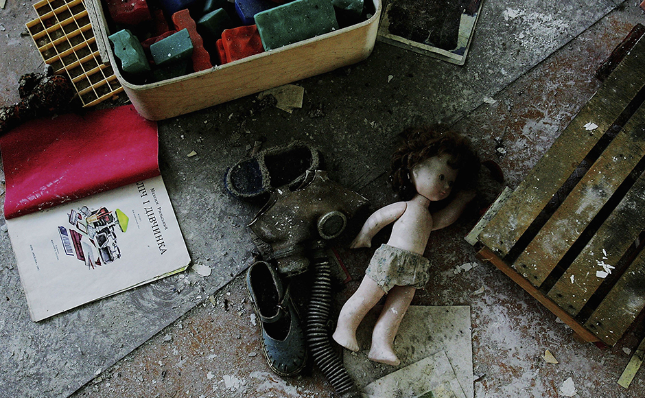 CHERNOBYL - JANUARY 25: Toys and a gas mask lay in dust in an abandoned pre-school in the deserted city of Pripyat on January 25, 2006 in Chernobyl, Ukraine. Prypyat and the surrounding area will not be safe for human habitation for several centuries. Scientists estimate that the most dangerous radioactive elements will take up to 900 years to decay sufficiently to render the area safe. (Photo by Daniel Berehulak/Getty Images)
