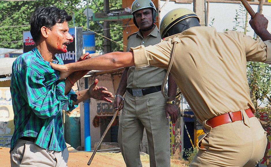 Police beating up one of the garment workers who were protesting over EPF withdrawal norm, in Bengaluru on Tuesday. PTI Photo by Shailendra Bhojak