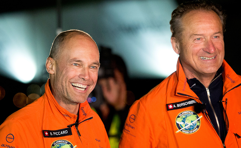 Solar Impulse 2 pilots Bertrand Piccard, left, and Andre Borschberg celebrate after Piccard landed their solar-powered plane at Moffett Field in Mountain View, Calif., on Saturday, April 23, 2016. The solar-powered airplane landed in California on Saturday, completing a risky, three-day flight across the Pacific Ocean as part of its journey around the world. (AP Photo/Noah Berger)