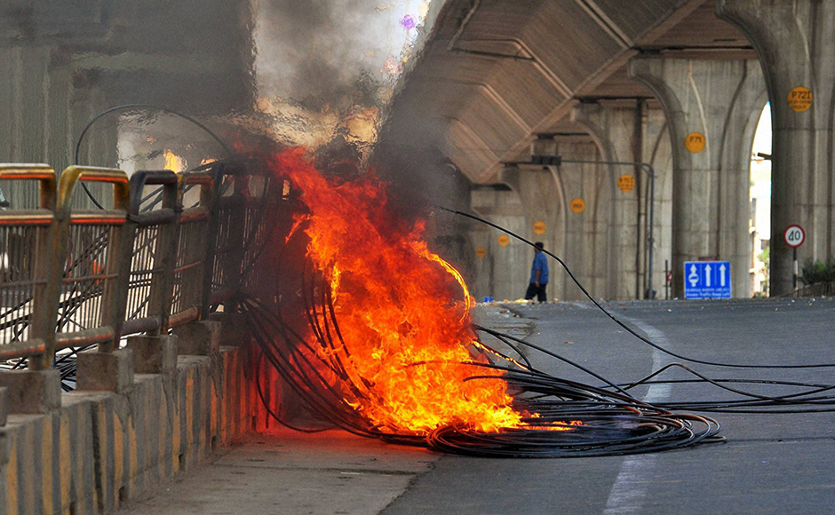 Cables in flames after being torched by agitating garment workers in a protest rally in Bengaluru on Tuesday. PTI Photo by Shailendra Bhojak