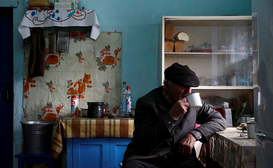 Ivan Shamyanok, 90, drinks tea in his house in the village of Tulgovichi, near the exclusion zone around the Chernobyl nuclear reactor, Belarus April 2, 2016. Shamyanok says the secret to a long life is not leaving your birthplace even when it is a Belarusian village poisoned with radioactive fallout from a nuclear disaster. REUTERS/Vasily Fedosenko
