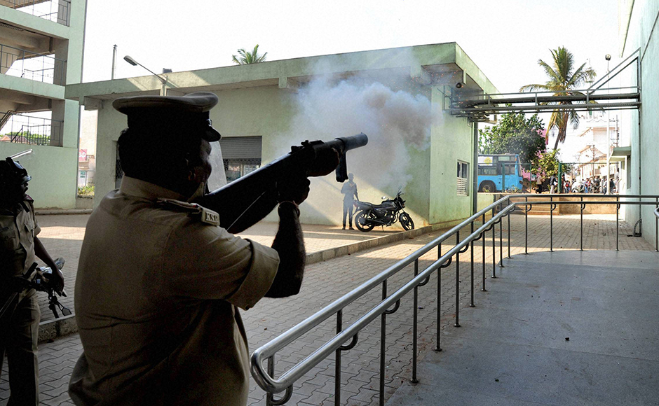 Police fire tear gas shells on garment workers who were protesting over EPF withdrawal norm, in Bengaluru on Tuesday. PTI Photo by Shailendra Bhojak