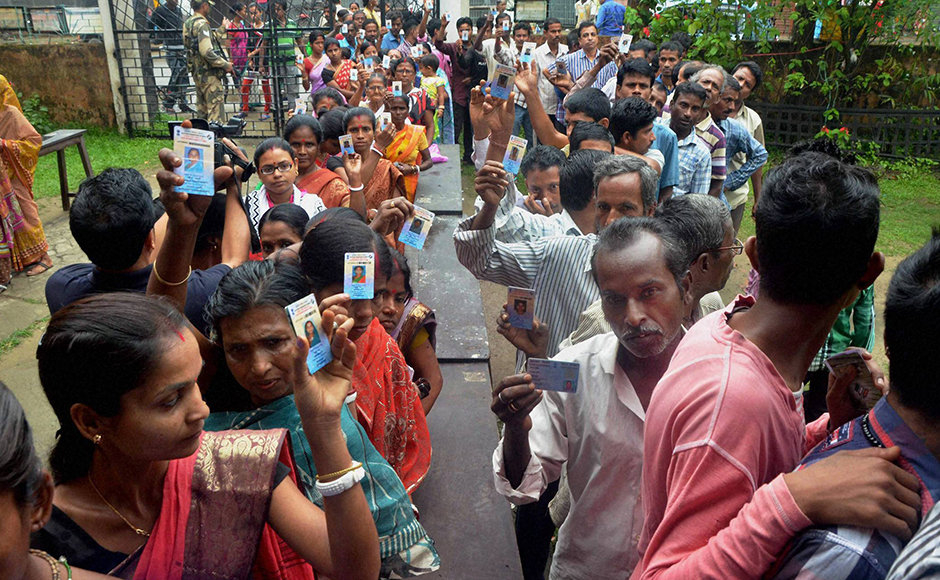Silchar: Voters stand in queue at a polling booth to caste their vote during the first phase of the Assam assembly polls in Silchar on Monday. PTI Photo