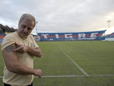 Argentina's Tigre soccer club directive Ezequiel Rocino, shows the place in his arm where he had a biochip implanted for testing, at Tigre stadium, in Buenos Aires. AP