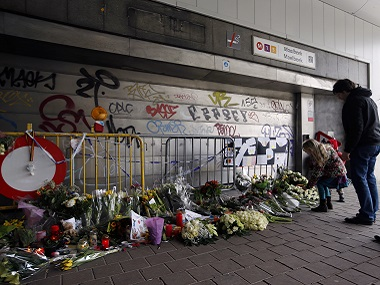 People stop and look at floral tributes placed outside the Maelbeek metro station in this file photo from March. AP