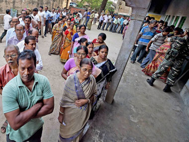 Voters stand in a queue to cast vote at a polling booth  during 4th phase of assembly polls in Howrah on Monday.  PTI