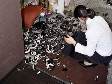 A woman collects fallen dishes at a restaurant after an earthquake in Kumamoto, southern Japan on Thursday. AP