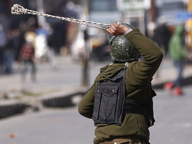 A policeman uses a slingshot to hurl stones towards Kashmiri demonstrators during a protest in Srinagar in February. Reuters