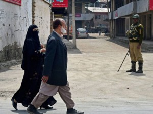 A couple walks at a road as a security jawan guards in a deserted street during the 4th consecutive day of strike and restrictions in Srinagar on Saturday. PTI