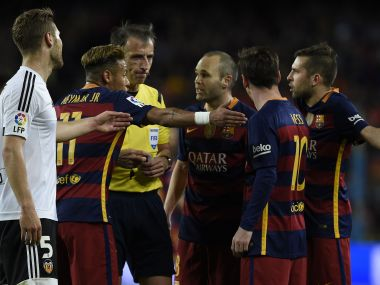 Barcelona players debate with the referee during their 2-1 loss to Valencia. AFP