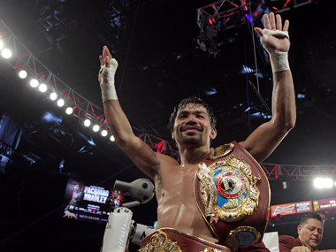 Manny Pacquiao gestures to fans celebrating after defeating Timothy Bradley Jr. in a 12 round unanimous decision. AFP