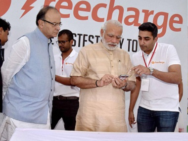 Prime Minister Narendra Modi makes e-payment for an e-Rickshaw ride while Union Finance Minister Arun Jaitley looks on, during the launch of Stand up India in Noida. PTI